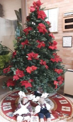 Green Artificial Pine Tree with Artificial Red Poinsettias with stuffed reindeer dressed in clothes